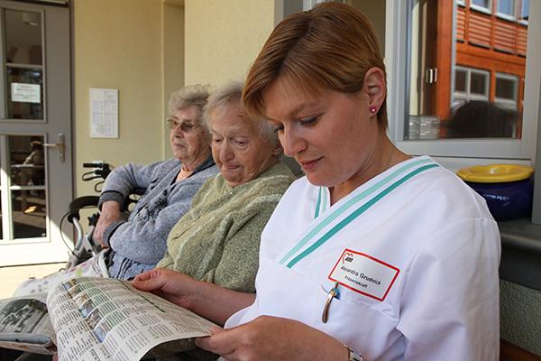 Senioren mit Betreuerin bei der Zeitungsschau