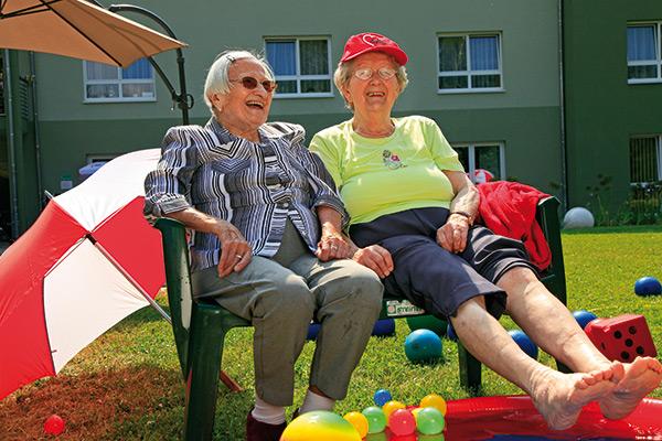 Zwei Seniorinnen sitzen auf einer Bank